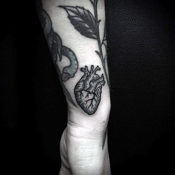 Male With Heart Tattoo On Wrist In Black Ink