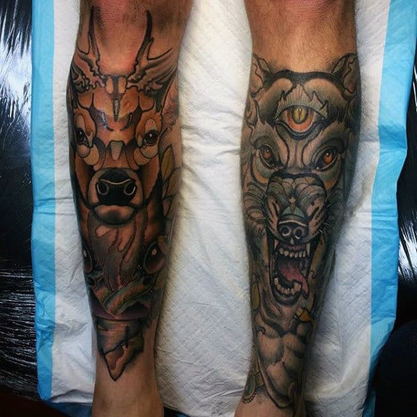 Male With Shin Tattoos Of Deer And Wolf
