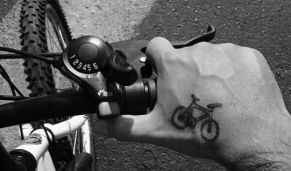 Male With Small Bicycle Tattoo On Hand