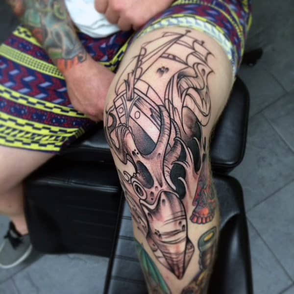 Male With Squid And Sailing Ship Knee Tattoo