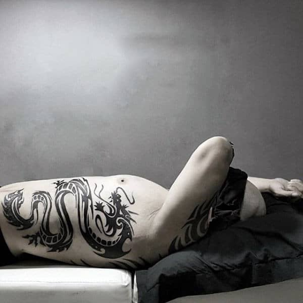 Male With Tattoo Of Black Ink Tribal Dragon On Ribs