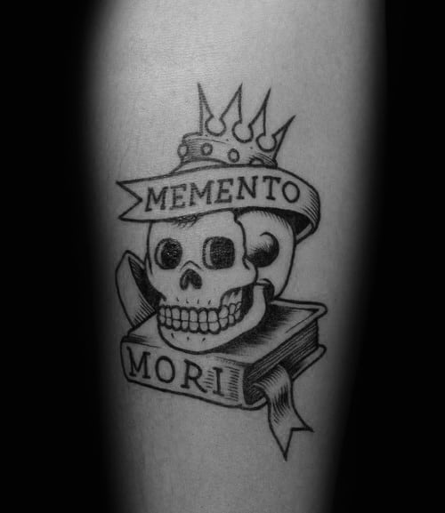 Male With Tattoo Of Memento Mori Skull And Books On Forearm
