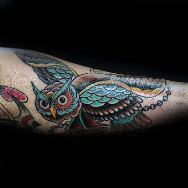 Male With Tattoo Of Owl And Chain Traditional Design On Outer Forearm