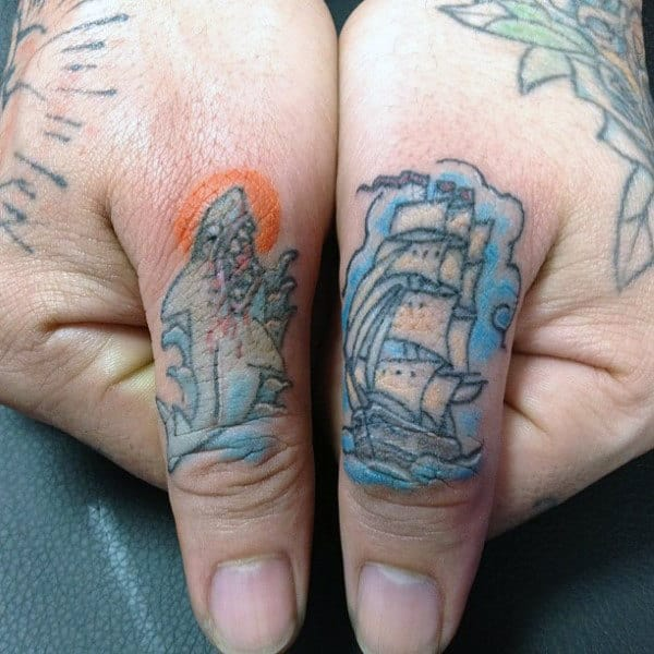 Male With Thumb Tattoos Of Shark And Sailing Ship