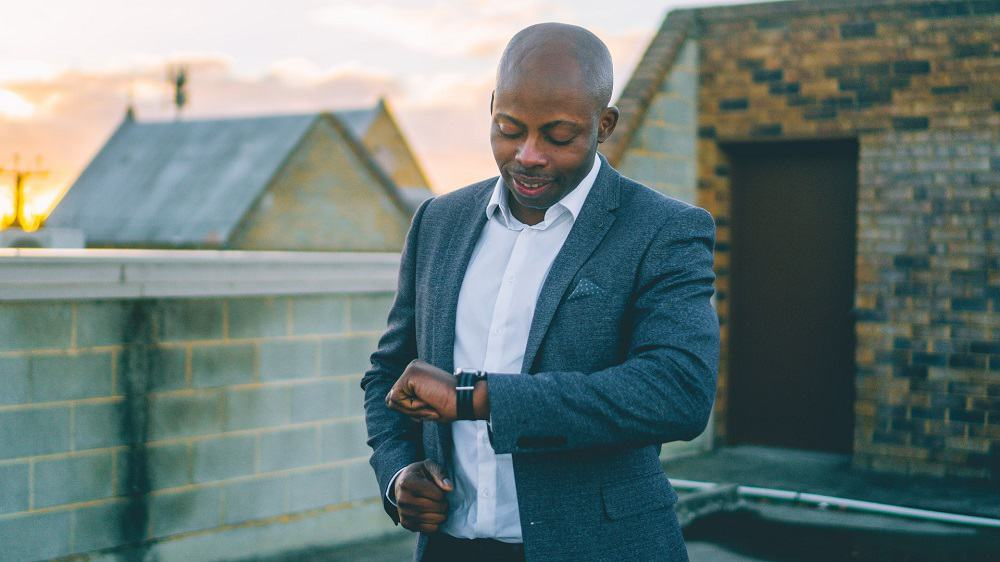 man on a rooftop checks his watch, wearing a grey blazer and white button up