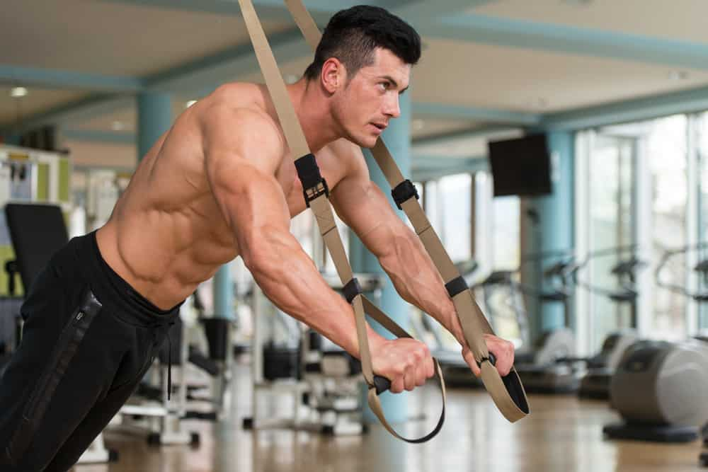 man does crossfit push ups with trx fitness straps