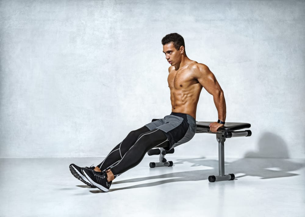 strong man working out arms muscles doing triceps dips using bench
