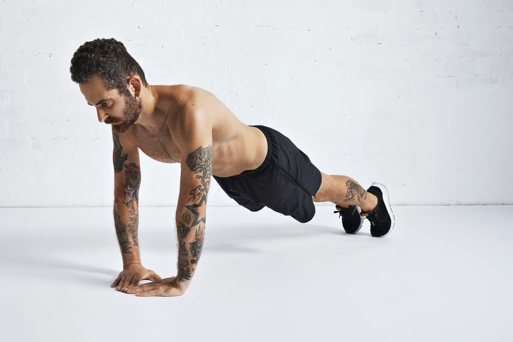 tattoed male athlete man doing diamond push up exercise