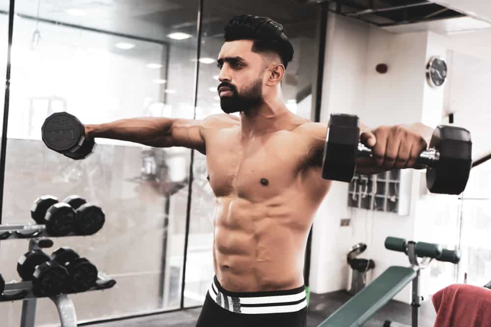 shirtless young man doing side lateral rises exercise in gym