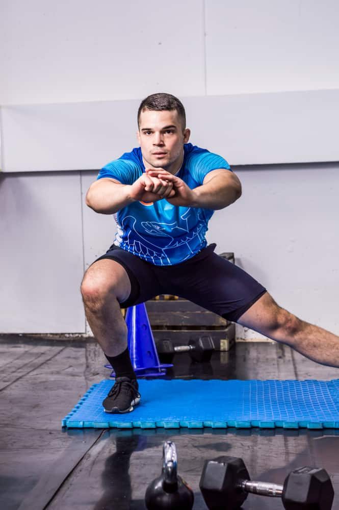 muscular young man doing side lunges at the gym