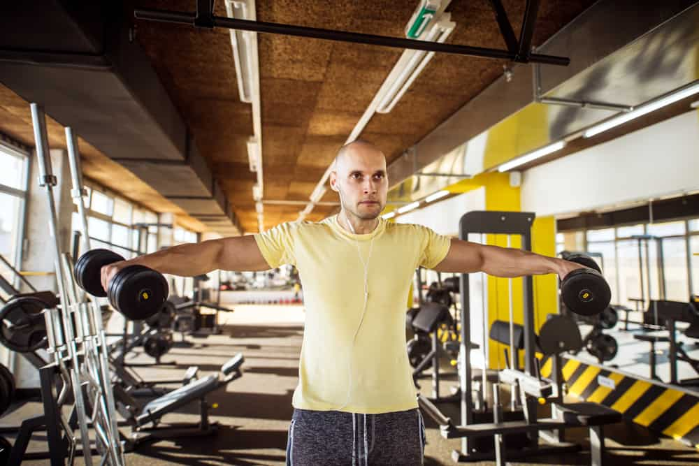 strong muscular man doing trap raise shoulder exercise in gym