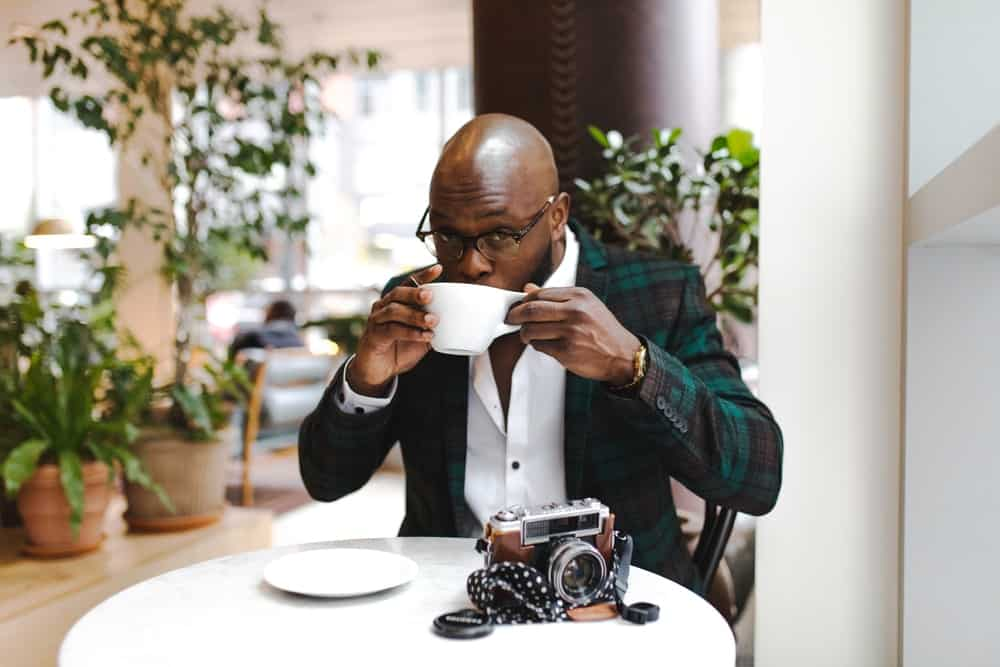 man sits in a cafe, drinking a coffee, wearing a green plaid blazer, and white button up