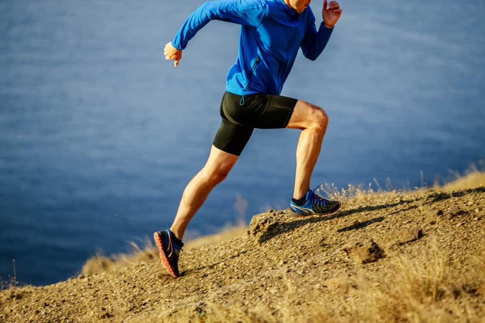 man dynamic running on steep slope of mountain