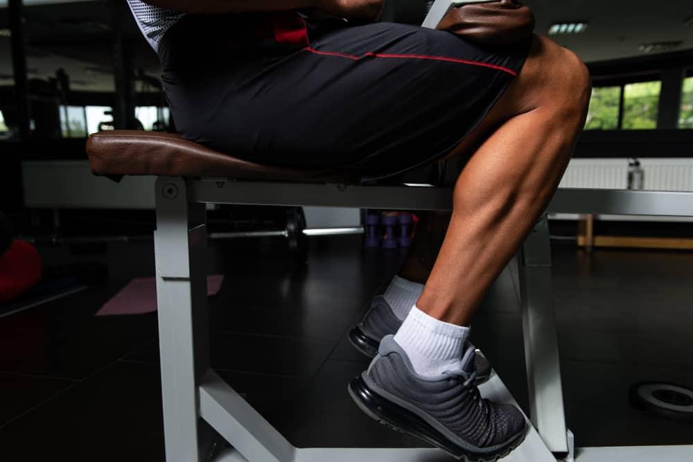 muscular man exercising calves on Machine in gym