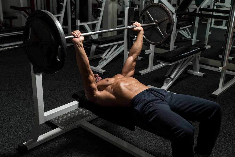 mature man in gym doing barbell bench press exercise