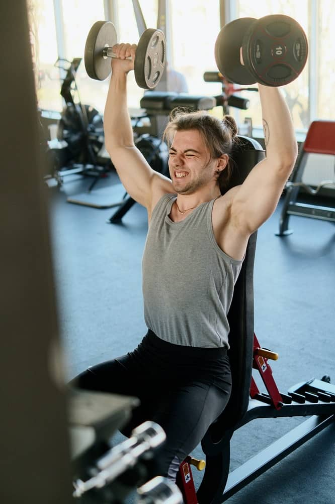 man exercising in gym with dumbbells