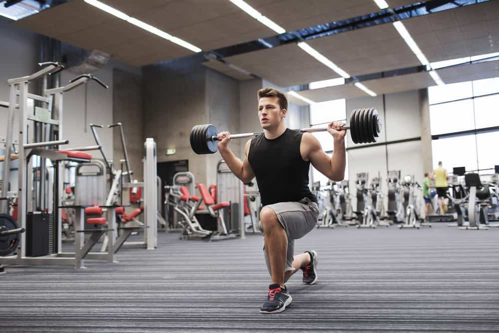 young man flexing muscles in gym