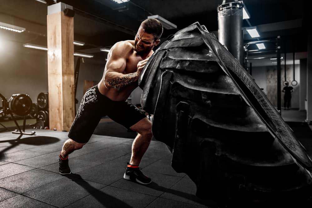 man flipping heavy tire in gym