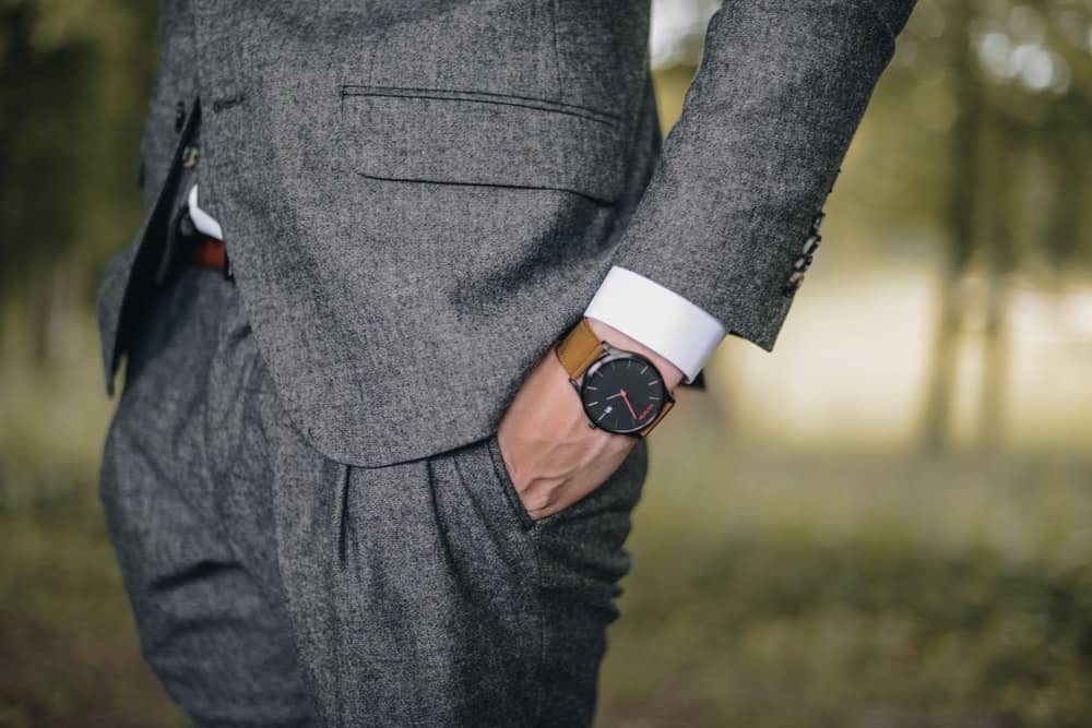 close-up show of a man with his hands in his pockets, focused on his watch. the watch has a clean black face and a plain brown strap