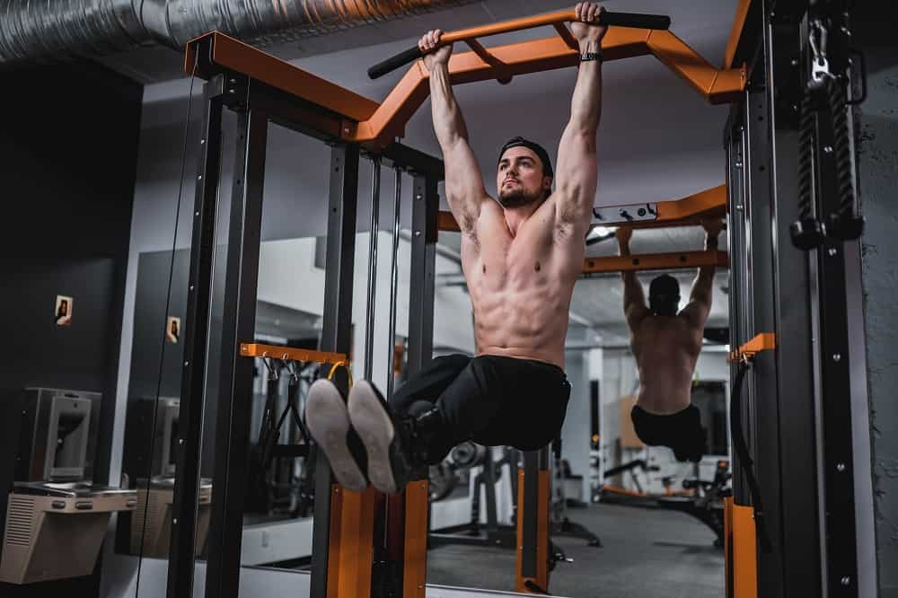 man hangs from a pair of pull up bars, legs raised parallel to the ground
