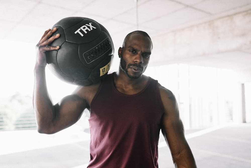 man stands alone, holding a medicine ball on his left shoulder