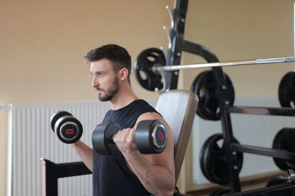 man holds a dumbbell in each hand, holding them upright towards his shoulders