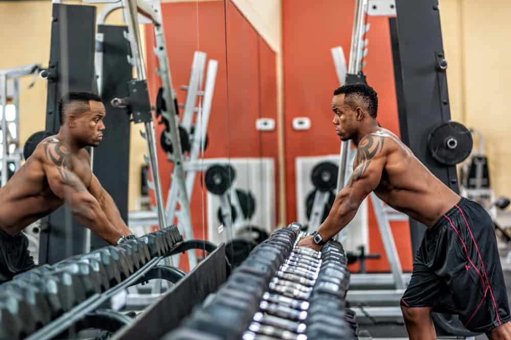 man in a gym looks are his reflection while picking up dumbbells from a rack