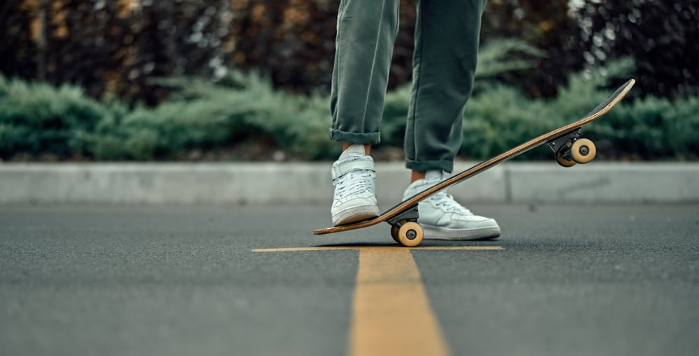 stylish man in white sneakers and green pants with a skateboard