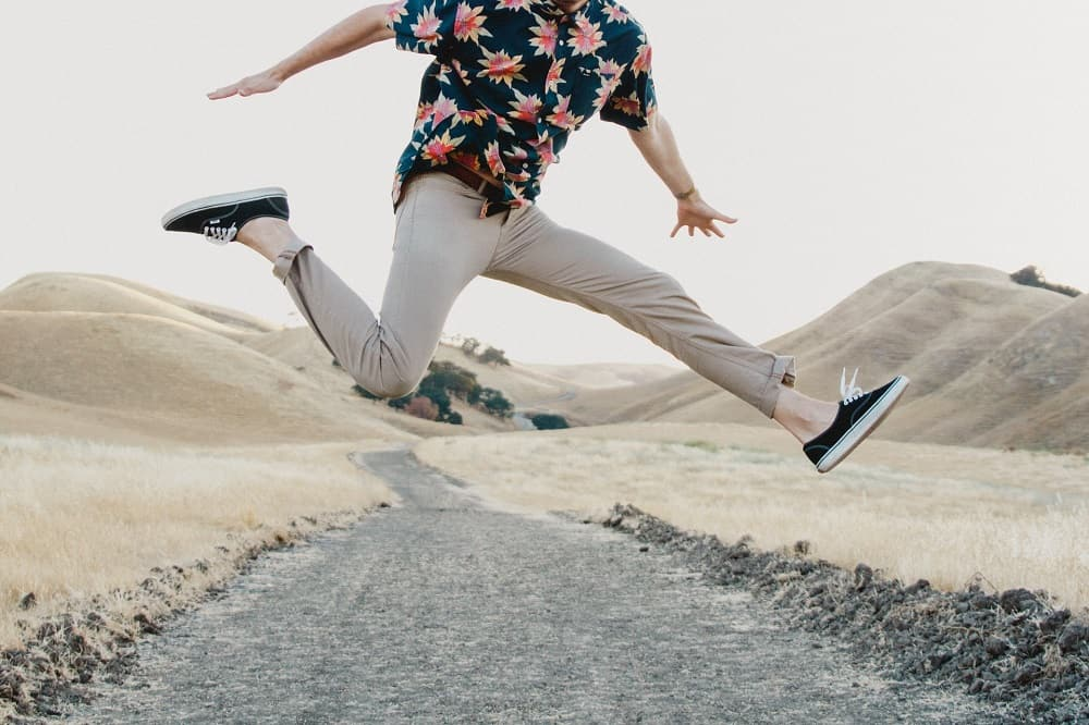 man jumping in mid-air, wearing khaki chino pants and a floral patterned button up shirt