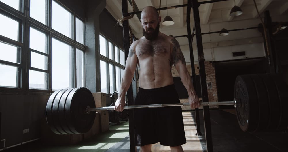 bearded caucasian man lifting heavy barbell in large hardcore gym hall