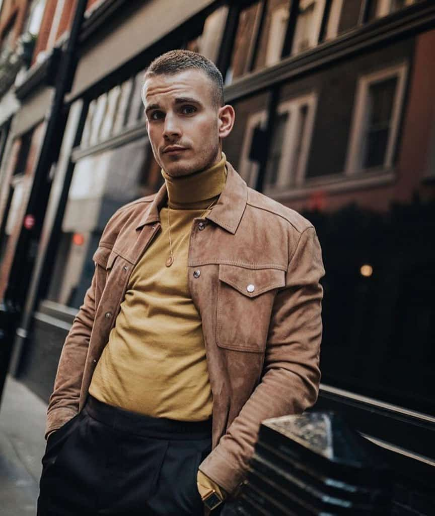 A man modeling a mustard-colored roll-neck shirt and a suede jacket