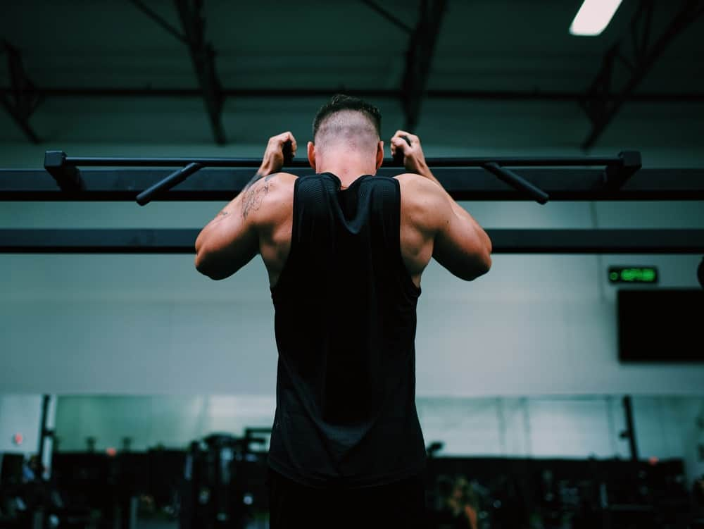 photo of the back of a man in a gym performing a chin up