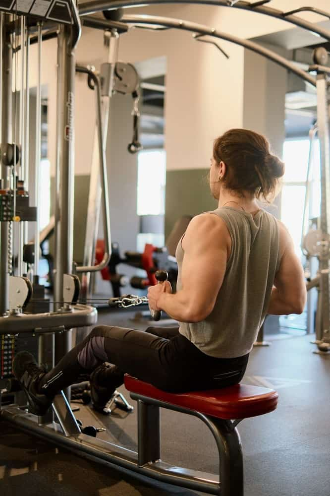man in a gym performs a cable row, sitting on the bench and pulling inward on the cable machine