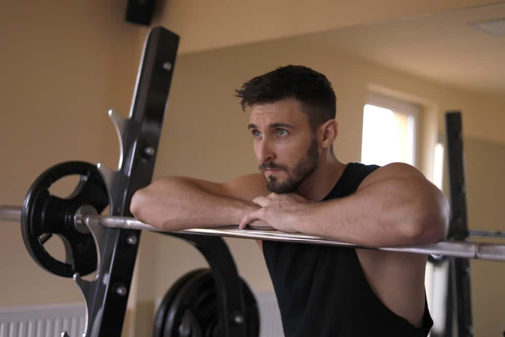 man rests his forearms on a barbell bar during training, looking forward