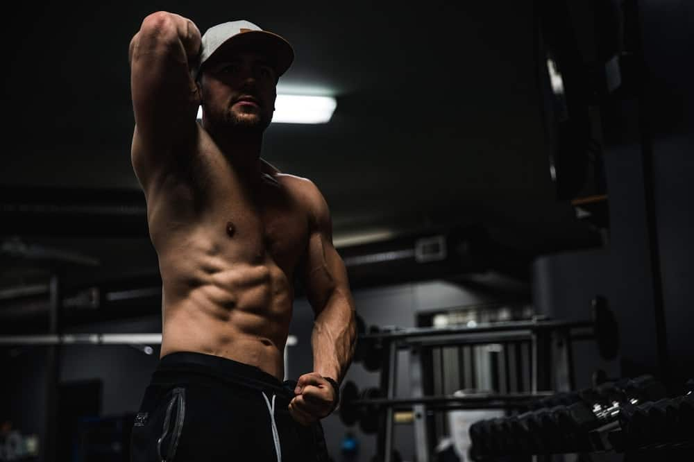 man poses in a gym, left arm flexed, right arm held up behind his head, showing off his abs