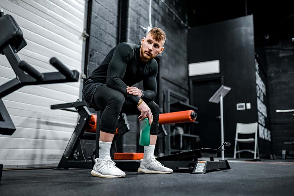 man in a gym sits on an exercise bench, holding a water bottle, arms resting on his knees