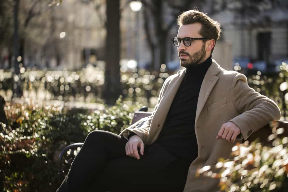 man sits on a park bench in black jeans, a black turtleneck, fitted tan trench coat, and back sunglasses