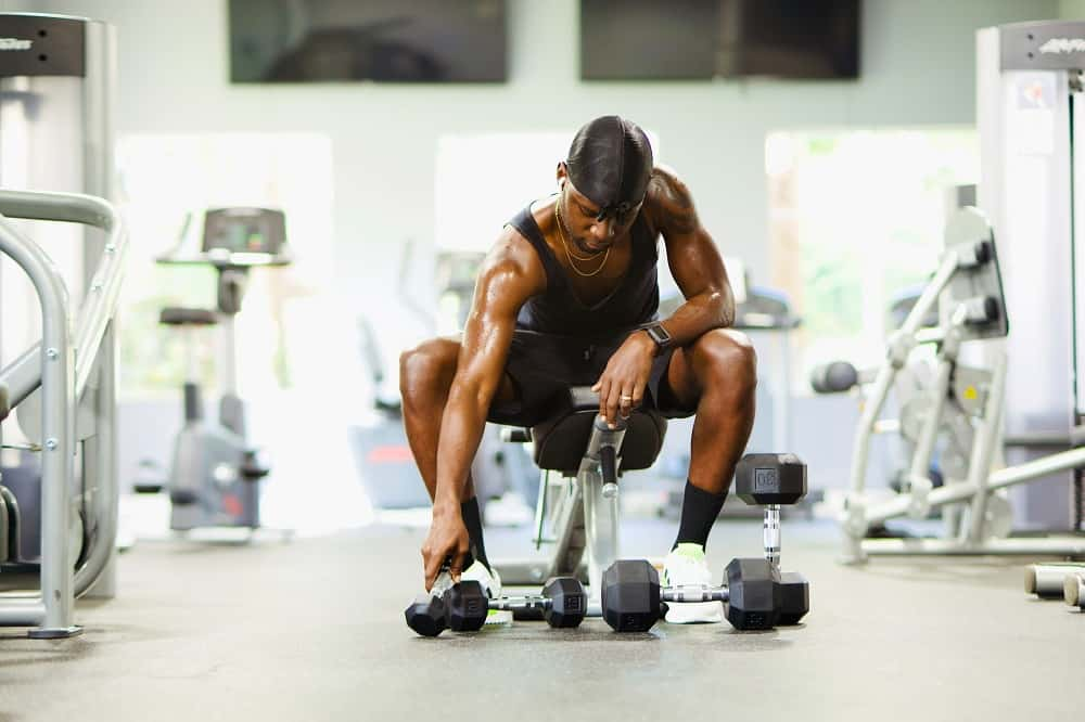 man in a gym sits on a workout bench, looking at various sizes of dumbbells on the ground below him