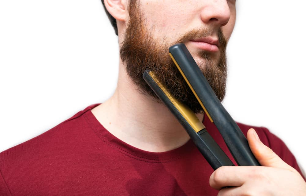 man straightened his beard with straightener, styling his beard