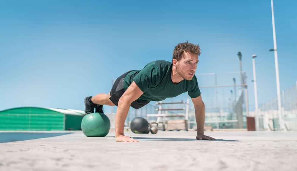 man strength training core doing decline pushup outdoor