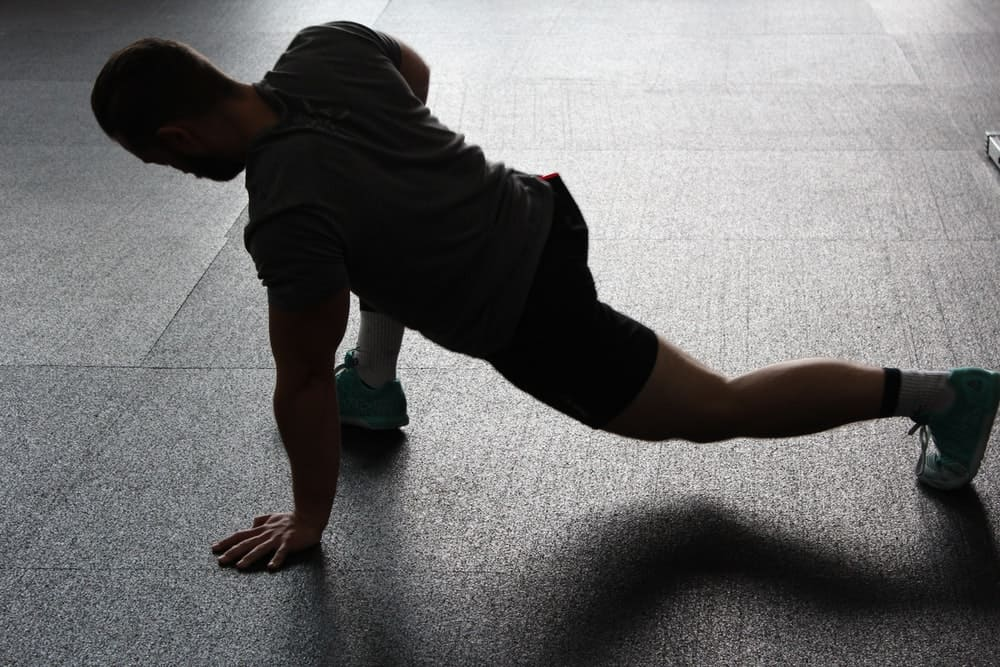 man in workout clothing stretches out his hamstrings before a workout