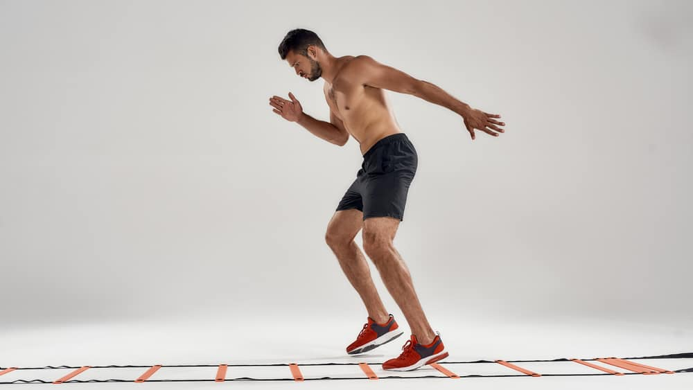 man training on agility ladder drill isolated over grey background