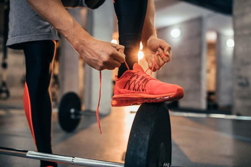 man tying his orange shoes shoelaces
