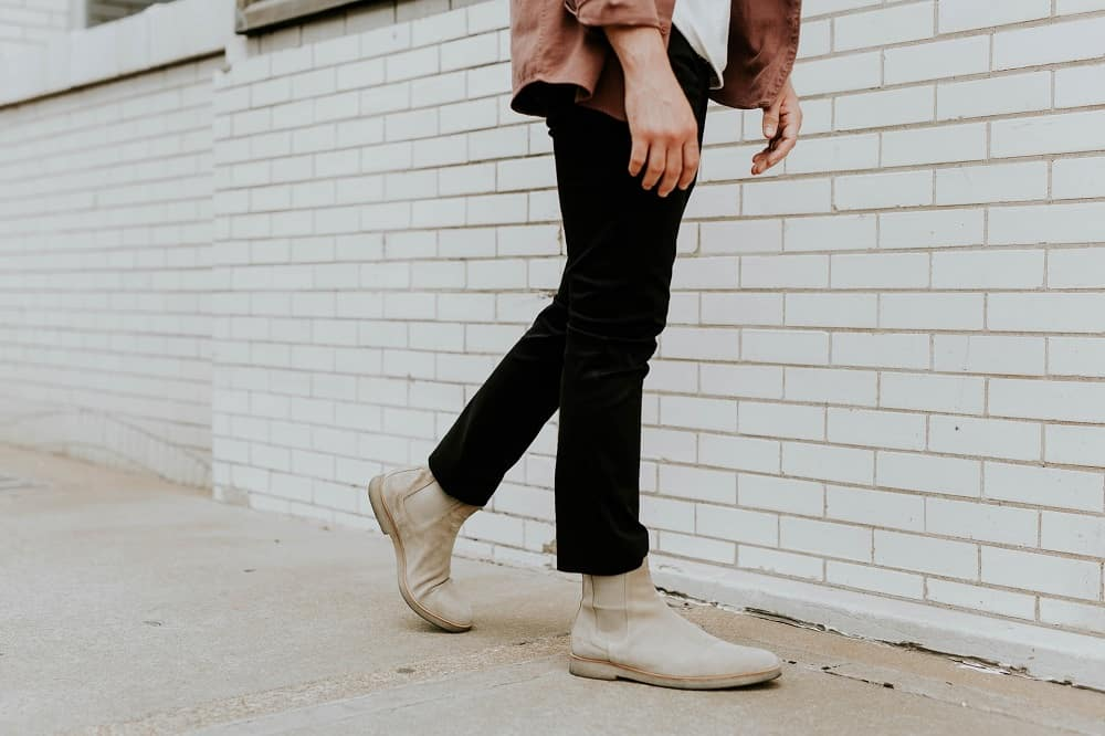 shot of a mans legs walking down the street, wearing black jeans and cream-colored Chelsea boots