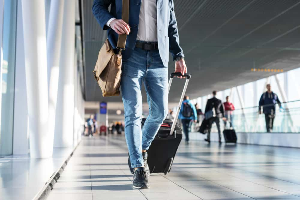man walking in airport with shoulder bag and hand luggage