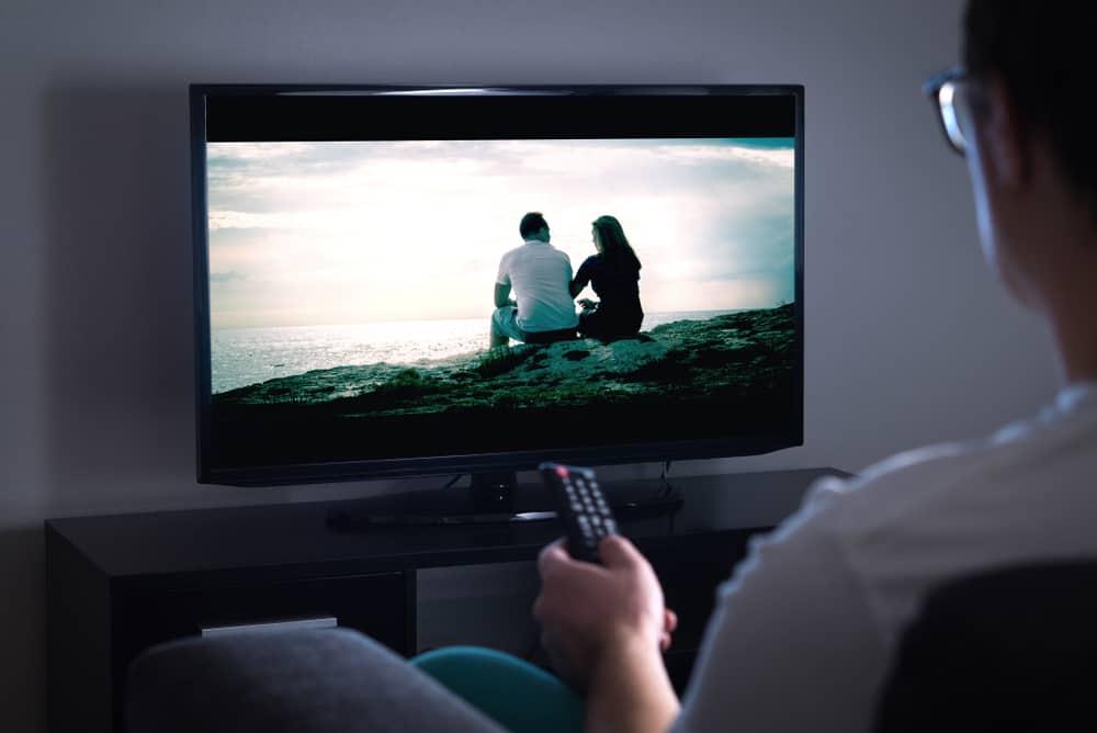 man watching movie on tv