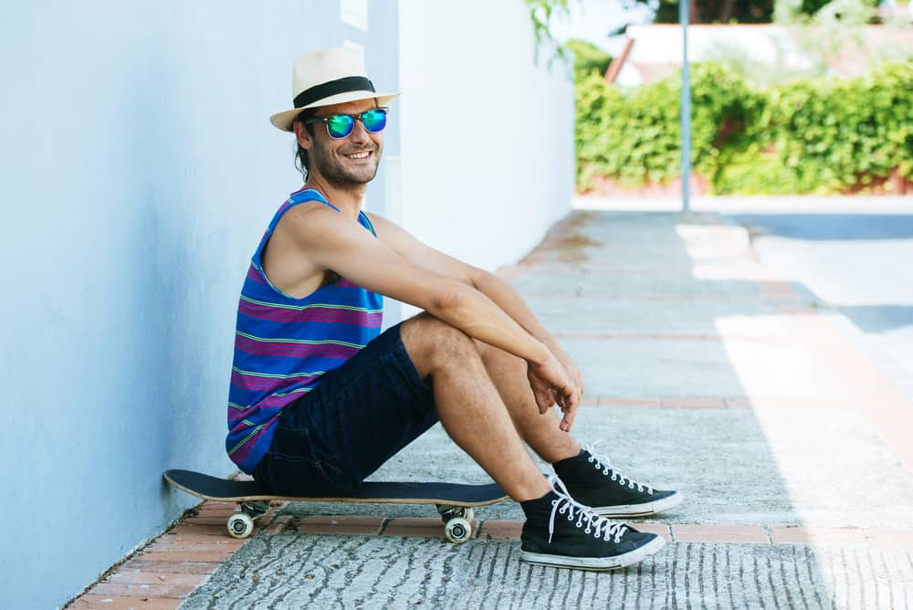 A smiling man wearing board shorts sitting on a skateboard