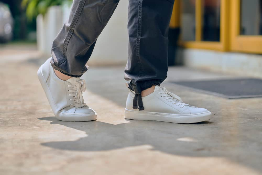 close up of man wearing white leather casual sneakers outdoor