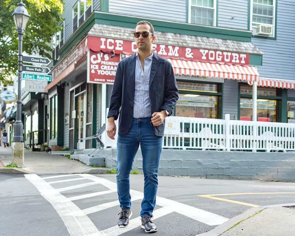 man crosses the street, wearing straight leg denim pants, a collared dress shirt, blazer, and sneakers