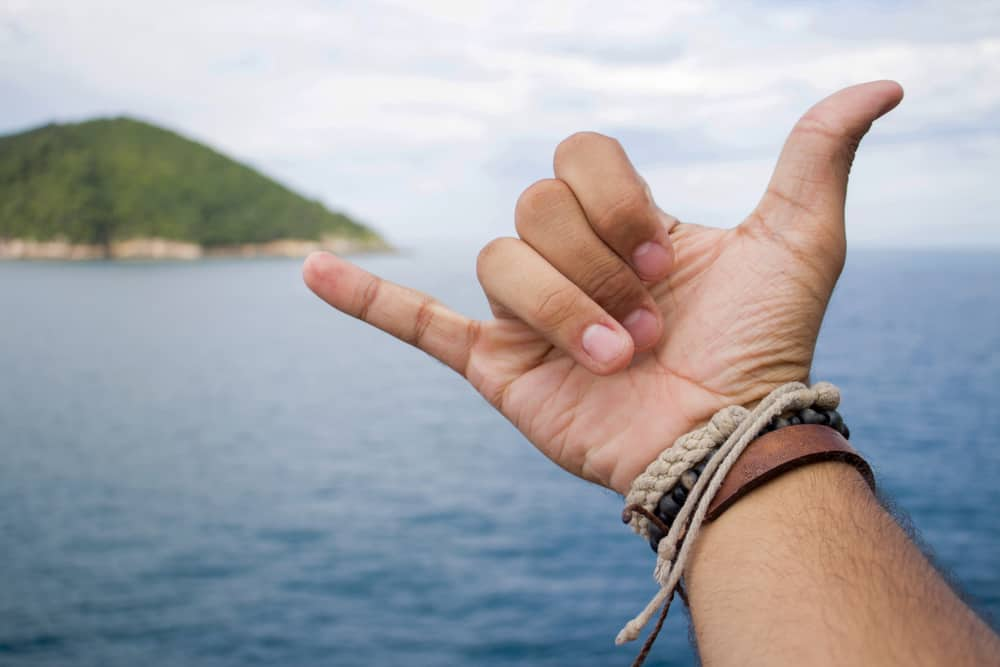 A man giving the shaka sign while wearing leather and hemp bracelets